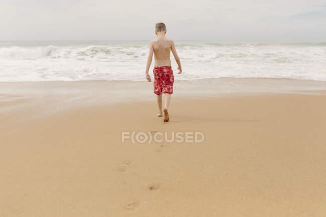 Boy walking on the beach — Stock Photo