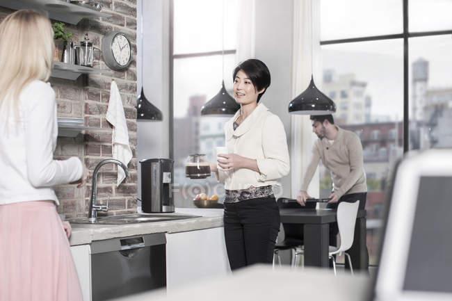 Друзья на кухне разговаривают за чашечкой кофе — стоковое фото