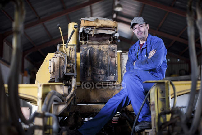 Man wearing blue overalls sitting on machine in workshop — Stock Photo