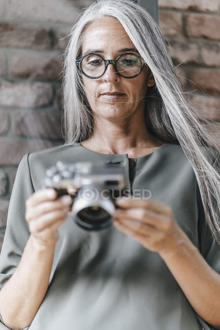 Close-up of Woman with long grey hair holding camera — Stock Photo