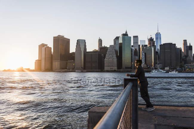Donna appoggiata su ringhiera e guardando la vista — Foto stock