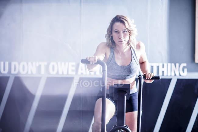 Junge Frau am Heimtrainer im Fitness-Studio — Stockfoto