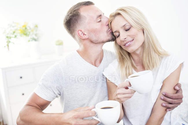 Man holding cup of coffee kissing woman — Stock Photo