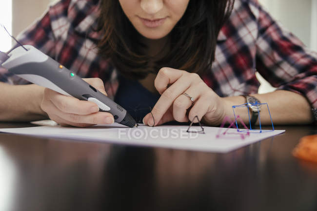Крупним планом уявлення про молоду жінку, малювання 3d пером, сидячи за столом — стокове фото