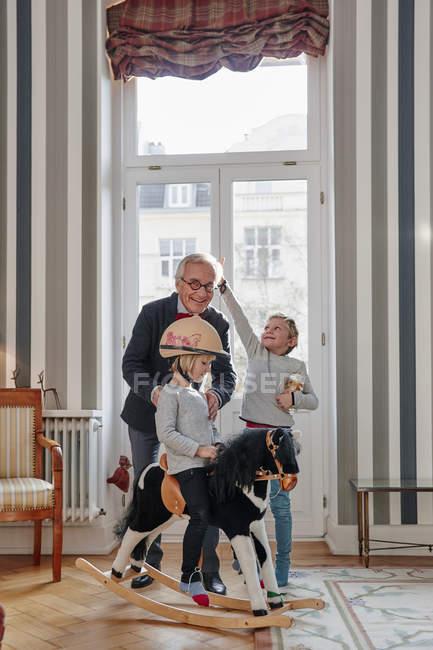 Abuelo y nietos jugando con caballo de oscilación - foto de stock