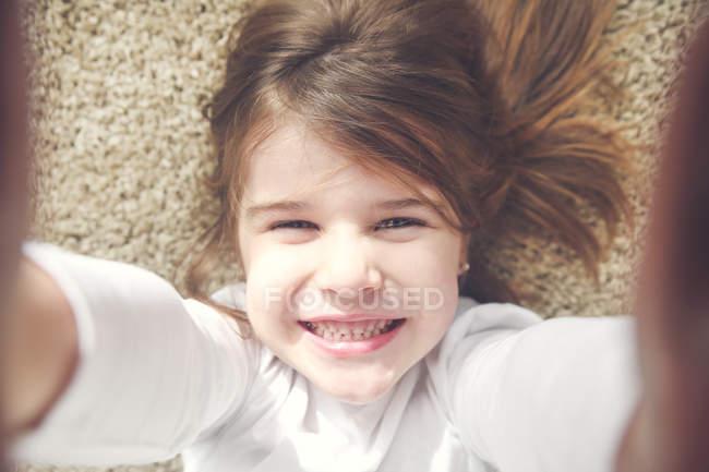 Porträt eines grinsenden kleinen Mädchens, das auf dem Teppich liegt und Selfies macht — Stockfoto