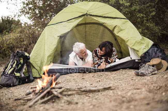 Happy senior couple lying in tent at campfire — Stock Photo