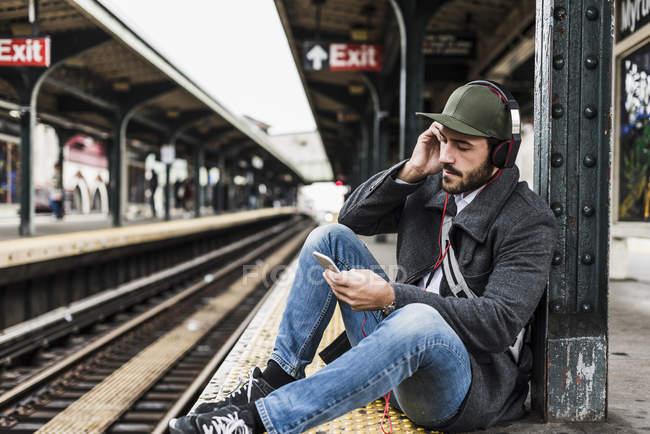 Молодой человек ждет метро на станции железнодорожной платформе, с помощью смартфона — стоковое фото