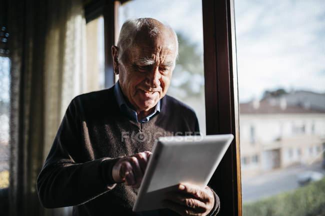 Старший мужчина с помощью планшета на дому, в расслабленном состоянии, рядом с окном — стоковое фото