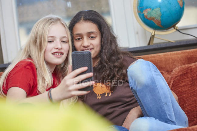 Two girls on couch sharing smartphone — Stock Photo