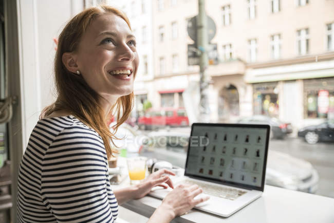 Smiling woman using laptop in a coffee shop — Stock Photo