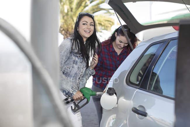 Deux femmes, voiture à gaz station de ravitaillement — Photo de stock