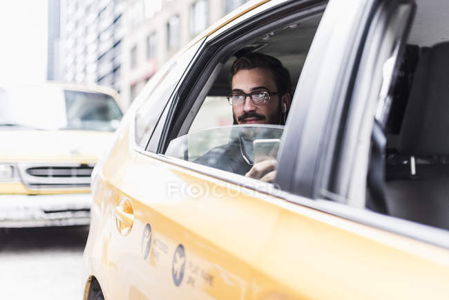 Uomo d'affari con cellulare e auricolari in taxi, New York, USA — Foto stock