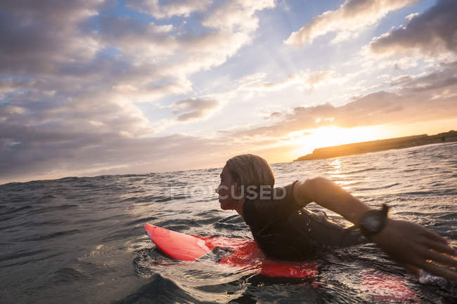 Adolescente nadando na prancha de surf no oceano ao pôr do sol bonito — Fotografia de Stock