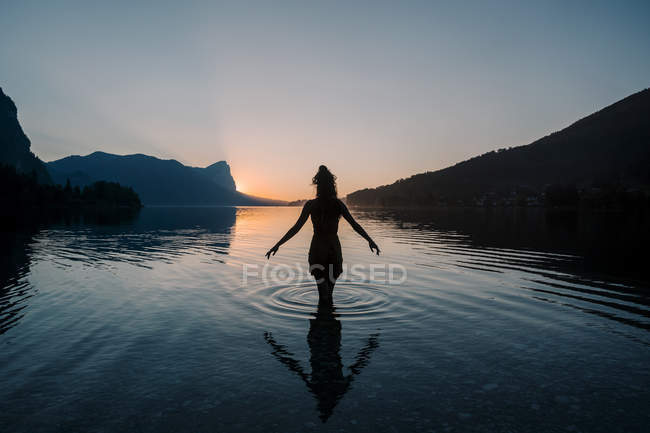 Silhouette of young woman standing in shallow lake water at sunset — Stock Photo