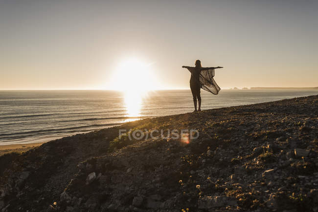Back view of happy teenage girl with arms outstretched standing on hill at sunset looking to the sea — Stock Photo