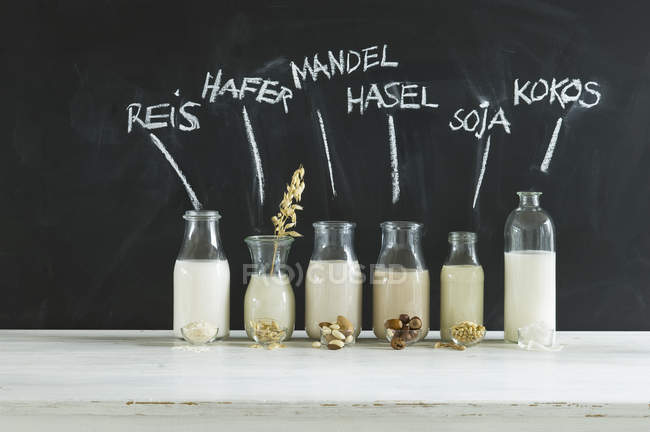 Стеклянные бутылки различных веганских молока — стоковое фото