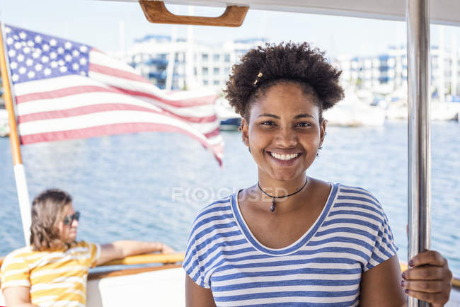 Smiling young woman on a boat trip with man on background — Stock Photo