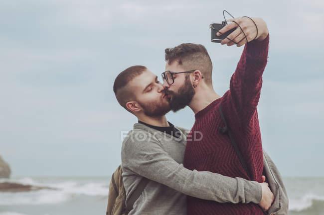 Гей пара беручи selfie під час поцілунку на березі моря — стокове фото
