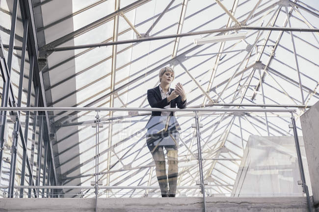 Businesswoman looking at smartphone in modern architecture — Stock Photo