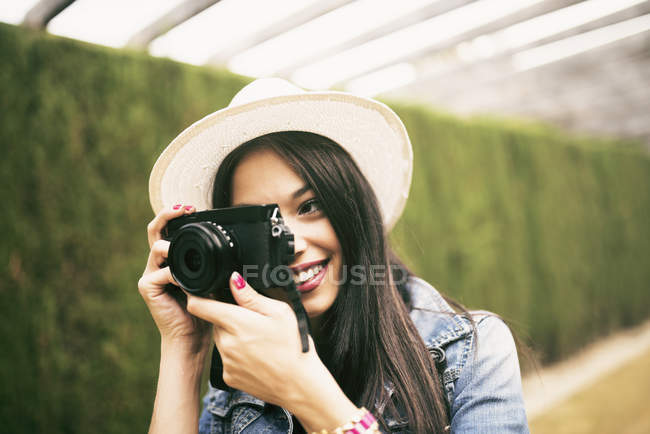 Young woman wearing hat taking picture with camera — Stock Photo