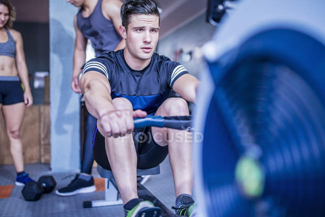 Young caucasian man exercising at rowing machine in gym — Stock Photo