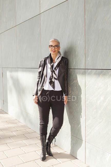Ritratto di donna matura alla moda appoggiata al muro — Foto stock