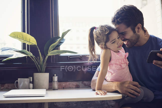 Father cuddling with toddler daughter sitting on table  holding smartphone — Stock Photo