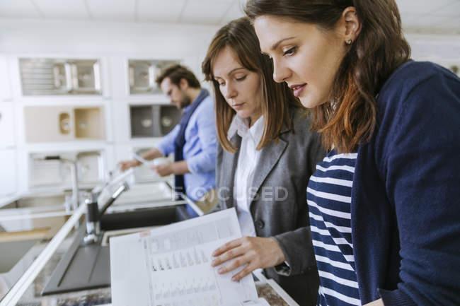 People in plumbing shop looking at kitchen sinks design — Stock Photo