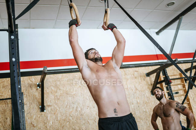 Caucasian sporty man doing exercises on rings in gym — Stock Photo