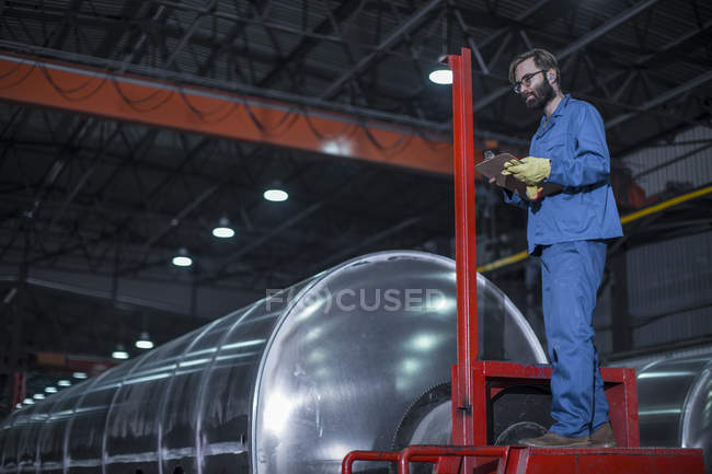 Worker with clipboard inspecting steel tanker in factor — Stock Photo