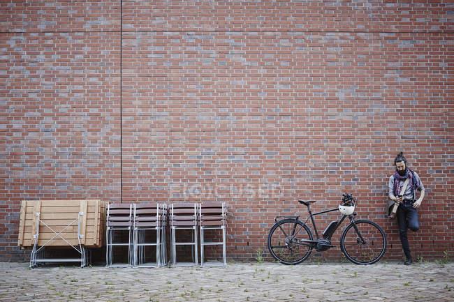 Portrait de cycliste à l'aide d'un téléphone portable près du mur de briques — Photo de stock