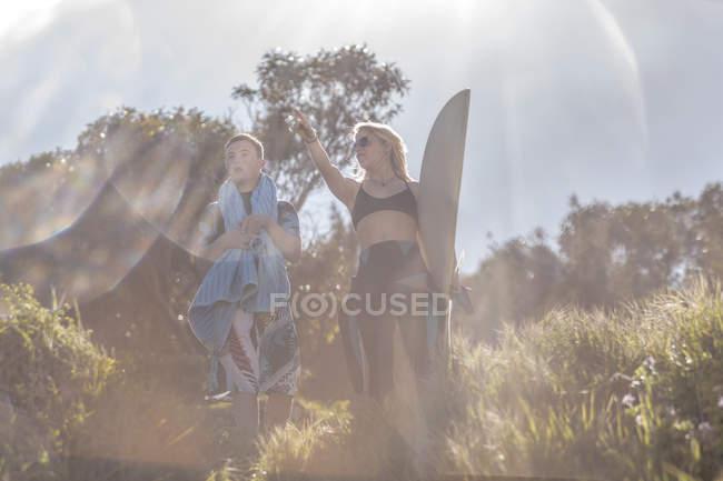 Adolescent avec le syndrome de down et de la femme avec planche de surf sur la côte — Photo de stock