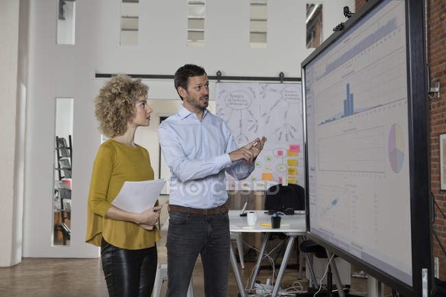 Man and woman discussing graphs on screen in office — Stock Photo