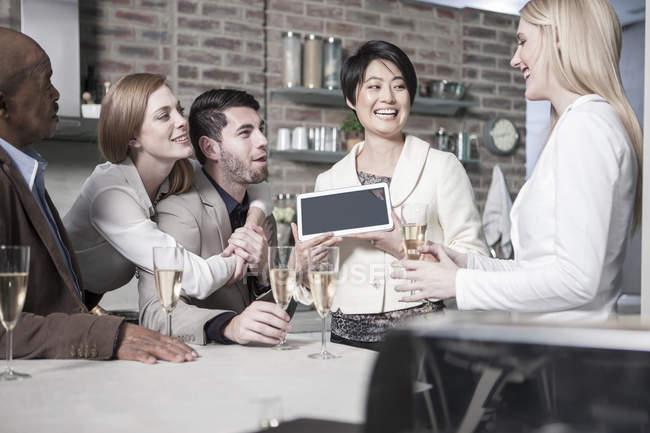 Щасливі жінка показ планшетний друзям з шампанським окуляри на дому — стокове фото