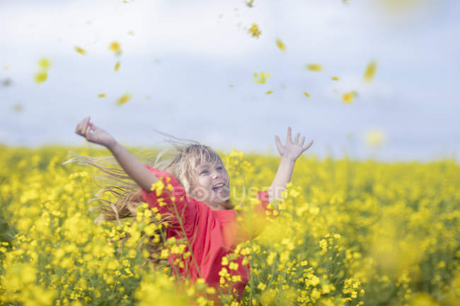 Happy little girl standing in rape field throwing blossoms in the air — Stock Photo