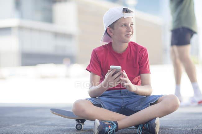 Ragazzo utilizzando smartphone mentre seduto su skateboard — Foto stock