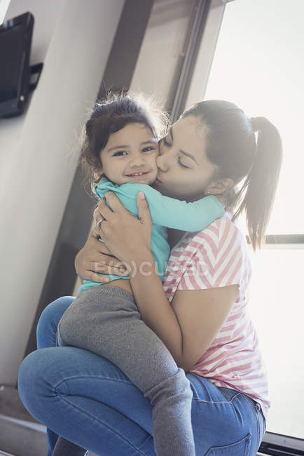 Mother kissing her toddler daughter in cheeck — Stock Photo