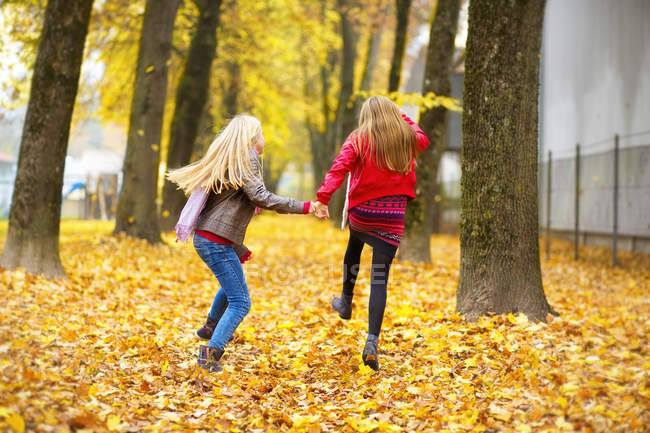 Back view of two jumping girls in autumn — Stock Photo