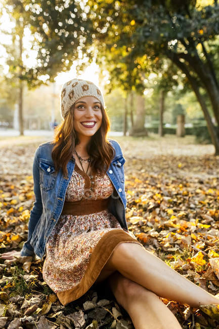 Giovane donna sorridente in un parco in autunno — Foto stock