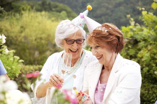 Старший пані п'є шампанське в день народження — стокове фото