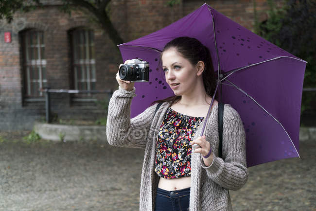 Young woman holding camera and umbrella outddors — Stock Photo