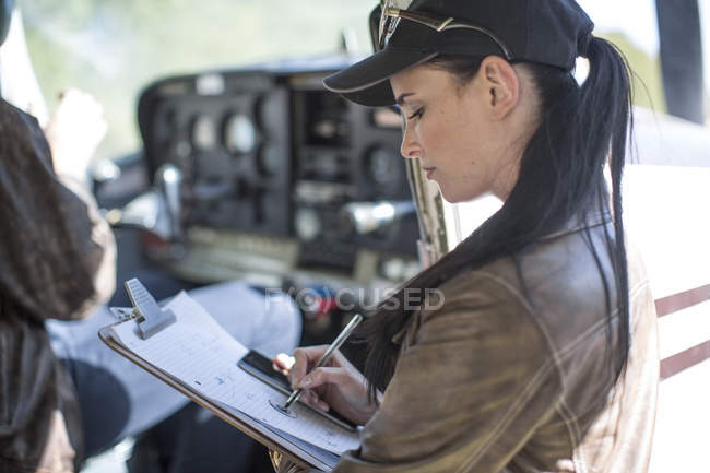 Молода жінка пілот оглядають легкий літак — стокове фото