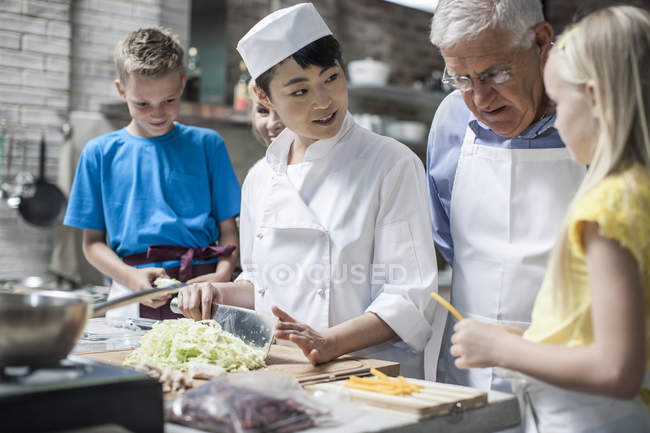 Chef instructs kids in cooking class — Stock Photo