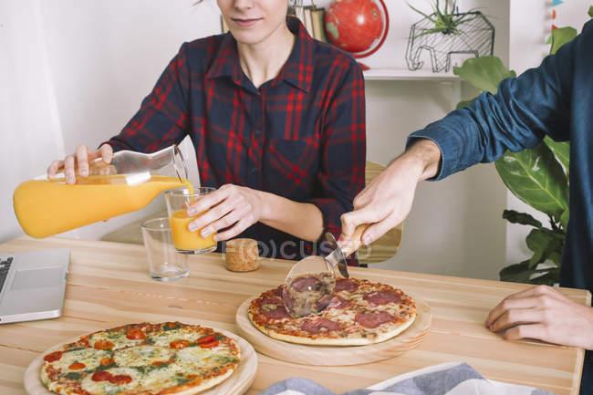Молодая пара едят пиццу и пить сок на обед — стоковое фото
