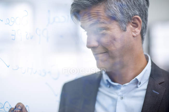 Office businessman writing ideas for project on glass — Stock Photo
