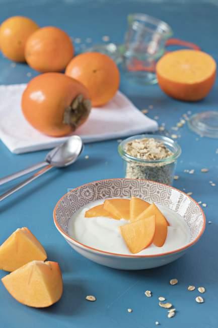 Closeup view of sliced kaki with yogurt and oat flakes — Stock Photo