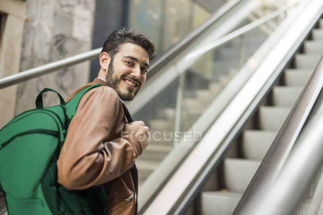 Homme souriant avec sac à dos debout sur l'escalator — Photo de stock