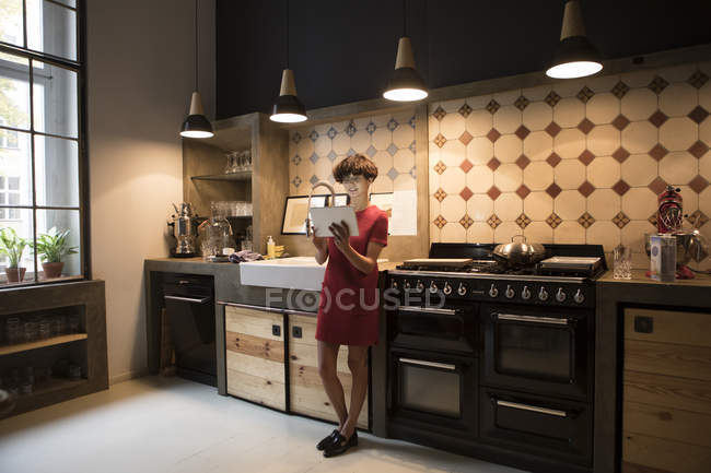 Mujer joven de pie en la cocina y el uso de tableta digital - foto de stock