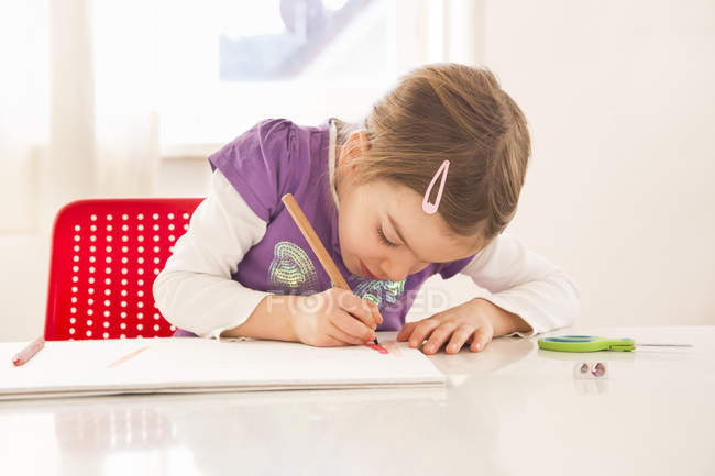 Little girl making a drawing on sheet of paper — Stock Photo